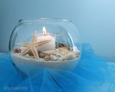 Beach Centerpiece - Wedding Decoration  This beach-themed centerpiece is surrounded by 1/2-yard of turquoise glimmer tulle. The glass bowl is 5-inches wide.