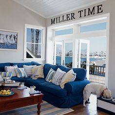 "Aside from the ""MILLER TIME"" letters, I like the colors---ties in with your yellows, greens, blues. The living room features nautical elements and a sea-inspired color palette. Durable cotton-duck slipcovers and a cotton rug in the family room make cleanup easy in case the party—or the dogs—get out of hand."