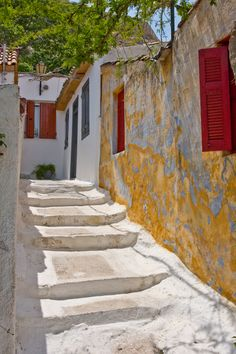 Anafiotika, Plaka, Athens Greece - walls are covered in layers of limewash - windows have wooden shutters to keep out the heat