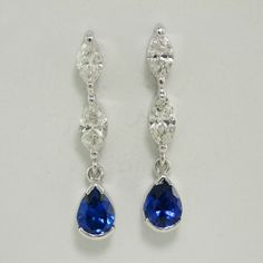 Tanzanite and Diamond Earrings. Top grade Tanzanite pear shapes in long hanging earrings, also featuring a pair of marquise cut Diamonds in each earring. Set in 18kt white gold.