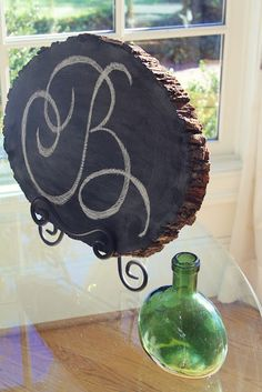Monogram tree slice using chalk board paint for wedding decor.