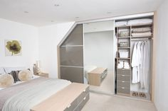 Fitted wardrobe with sliding door - bespoke design, installed under the eaves in an attic room, with built in drawers and shelving - photo from a trusted supplier of sliding doors, used by Alcove Designs.