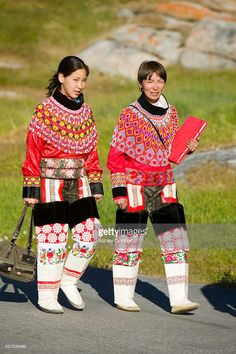 Inuit women wearing traditional Greenlandic national costume or Kalaallisuut in Ilulissat on Greenland. The costume consists of seal skin boots(Unnaat) bead necklaces (Nuilaqutit) and seal skin tr.