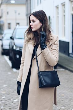 Tan coat, black blouse, black trousers, black gloves, and black cross body bag