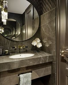 We love a bit of drama in a guest bathroom, here with marble slabs over textured wallpaper and round mirrors on both walls . - Amanee Ammar - We love a bit of drama in a guest bathroom, here with marble slabs over textured wallpaper and roun - Bathroom Design Luxury, Modern Bathroom, Stone Bathroom, Industrial Bathroom, Bad Inspiration, Bathroom Inspiration, Guest Toilet, Circular Mirror, Bathroom Layout