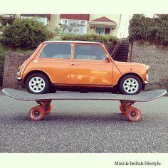 An orange classic mini cooper skating down the street on a giant skateboard!! haha