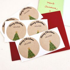 """This listing is for a pack of round stickers with a Christmas tree drawing and the text """"Merry Christmas. Love & Peace"""". These stickers are perfect for adding a lovely note to your homemade holiday gi"""