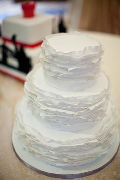 My cake is going to be ivory with three tiers of this ruffle texture in fondant, and in between will be two half tiers of smooth fondant. Pearl piping between each tier, and a flower topper. Maybe sparklers for cutting?