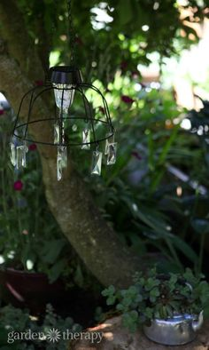 Solar light chandelier project hanging in the play garden - Make this project in no time with a few common materials and then let your imagination run wild in decorating it.