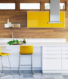 White and yellow kitchen against a wood-effect wall.