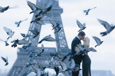 Amazing engagement session in front of the Eiffel tower with birds flying around. Creative photography for great couples