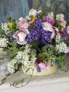 Ivy, blossom, magnolia, hyacinths, grape hyacinths arranged in an old baking dish