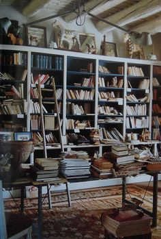 Our sloppy piles of books would look so much better if we had ceiling beams, floor-to-ceiling bookshelves, a farm table, and a gorgeous rug.