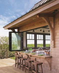 Not all home bars are indoors. This one is located on a lovely scenic deck, with an accordion window that can be closed in case of inclement weather.