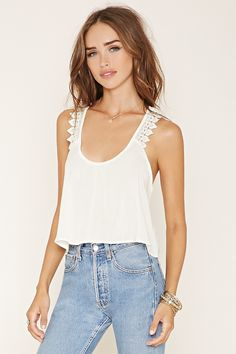 A sleeveless woven top with scalloped crochet straps that crisscross at the back and a scoop neckline.