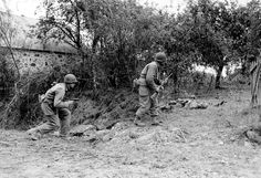 Two German KIAs lie in the path of US troops cautiously approaching after having received fire from a German sniper near Saint-Lo, France, summer 1944. Note the M1A carbine and the Colt .45 carried by the GIs.