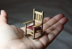A 1:24 (half scale) miniature rocking chair made of coffee stirrers.
