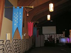 Stamped dollar store tablecloths turned into flags.  My husband made trumpets made of extra long, heavy duty funnels from Walmart (in the automotive dept.) which fitted perfectly into plastic pvc pipes and painted gold.  Total cost around $4 each including gold tassels.