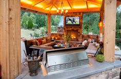 Such a cozy #outdoor #kitchen with TV. Like the warm feeling of this area because of its fireplace.