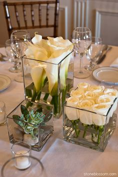 White roses cut short and lined up in short square glass container, taller square with taller white callas and succulent in smallest square vase