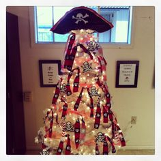 Pirate Christmas Tree! I decided to go with our Mascott this year. Cost...$0 My students faces...priceless! My mother-in-law gave me the pre-lit tree, already had the fabric, cut into strips and tied on the tree, toile ribbon in red and black....got that from my wife's stash, inflatable pirate hat, and bulletin board Jolly Roger's made into ornaments!