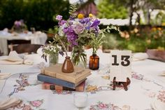 Wedding Decor: Old books, flowers in ink jars, and favorite quotes on napkin rings. Love love love...