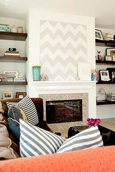 Grey stripe and navy blue pillows make a brown couch more fresh and slightly beachy especially in a white room