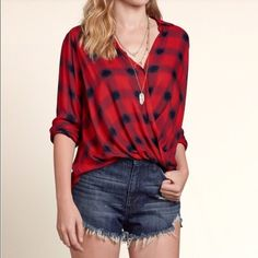 4TH SALE LAST DAY! Hollister Plaid Wrap Shirt Hollister Red Plaid Wrap Front Shirt! This is such a fun twist on a basic red plaid shirt. Definitely a must have for the summer - I can definitely see wearing this to an outdoor concert! Brand new with tags, still in plastic packaging.  credit: Hollister.   NO TRADES NO OFF SITE  ✅POSH RULES ONLY ✅FAIR OFFERS  PLEASE USE OFFER BUTTON!  ❓ASK IN THE COMMENTS!   BUNDLE 2+ ITEMS & SAVE!!!!! Hollister Tops