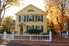 yellow house, white picket fence, blue shutters, fall leaves.