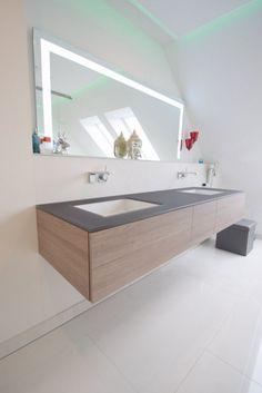 Damit der Badspiegel passend zur Waschtischanlage von Alape unter der Dachschräge passt, wurde er auf Maß von der Firma J-Mirror gefertigt. Dies war sehr einfach zu realisieren und als Option gab es noch eine Uhr im Spiegel. Der Spiegel ist mit einer indirekten Beleuchtung versehen und gibt so ein angenehmes Licht. Alape Waschtisch Möbel Holzdekor Graueiche mit Unterbaubecken, Trägerplatte rauchglas satiniert in braun. Drei Schubladen mit Verschlußautomatik und viel Platz für Badutensilien.