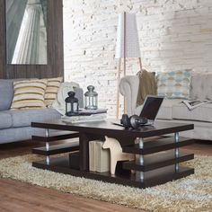 This architecturally inspired design coffee table features a uniquely detailed design with multi-shelving units. The table also has a nicely chosen dark espresso finish, with silver finish cylindrical accent supports.
