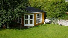 Im großzügigen Garten wirt auch ein großes 5-Eck-Gartenhaus dezent. In Naturholz mit weißem Anstrich für Tür- und Fensterrahmen wirkt es besonders natürlich.