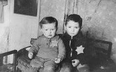 Due  fratellini posano per un ritratto di famiglia, nel ghetto di Kovno. Un mese più tardi saranno entrambi deportati nel campo di concentramento  Majdanek. Kovno, Lituania, Febbraio 1944.