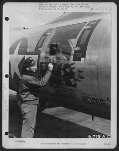 S/Sgt. Henry Warden from the 452nd Bomb Group putting the finishing  touches on the artwork around his waist gun position.