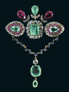 Emeralds, one rectangular on a bed of rose-cut diamonds, the other two almond, surrounded by rubies and diamonds. Three flowers, one set with an emerald and two rubies crown pin. A string set with small sapphires holds a pendant emeralds. 19th century.