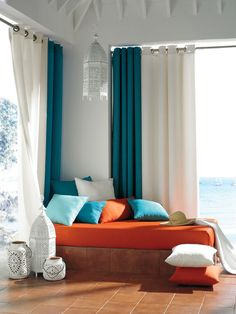 This is a great example of experimenting with curtains in two contrasting colors, and in this case the teal-green curtains placed in the corner anchor the seating area as well as provide a stronger shield from the sun when drawn. Who wouldn't want to take a little midday nap here?