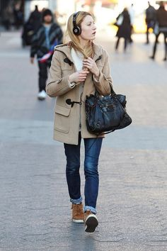 camel duffle coat, rolled jeans, and headphones