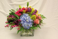 Hydrangeas, roses, tulips, lizianthus, heather, solidago in a clear glass cube