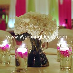 Wedding Centerpiece - hydrangea and calla lilies in a bow tie vase - votive candle accents with fuchsia orchids and small floating candles Purple Wedding, Our Wedding, Wedding Flowers, Dream Wedding, Wedding Stuff, Lily Centerpieces, Wedding Centerpieces, Vases, Bridal Party Tables