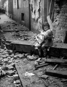 Une petite fille avec sa poupée assise sur les ruines de sa maison bombardée à Londres en 1940