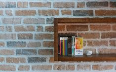 Living room brick wall with floating wooden shelves inside the smart attic apartment