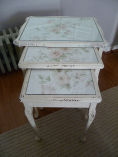Shabby chic nest of 3 tables.    These antique wooden tables have matching floral designs under their glass tops and pretty delicate legs.  Finished in aged effect antique cream.