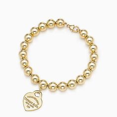 Return to Tiffany® small heart tag in 18k gold on a bead bracelet.