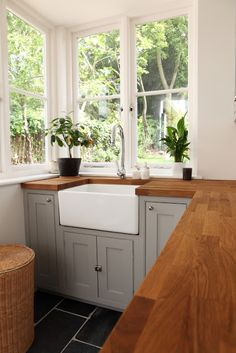 gray kitchen cabinets with butcher block countertops and white sink