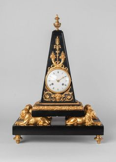 A French Empire black marble and bronze clock, of Egyptian taste by Faizan, 19th century, the case of obelisk form, supported on four lions with a rectangular marble base on turned feet, applied with a plaque with entwined cornucopia and female masks, the enamel dial with domed glass door, with Roman numeral chapter ring signed Faizan a Paris, the twin barrel movement with count wheel and bell strike, with key and pendulum - Dim: 49cm high