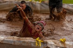 "Airman 1st Class Austin Jeanneret crawls through a mud puddle during a ""Tuff Mudder"" challenge Sept. 17, 2012, at Lajes Field, the Azores, Portugal. This year, Lajes Field kicked off the Combined Federal Campaign season with a Tuff Mudder challenge. Jeanneret is assigned to 65th Communications Squadron."
