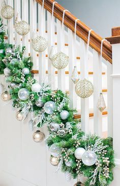 Make your staircase garland display unique. Use zip-ties or twine (avoids scratches) to attach garland at the base of the railings close to the stair treads instead of on the banister. Load it with Christmas ornament balls, picks and berries. Then balance it out with ornaments hung individually from the banister with Christmas ribbon. The cascading effect of this white-and-silver display is frosty elegance.