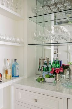 Built in shelves face a white wet bar accented with polished nickel knobs and topped with white marble countertops reflected in a mirrored backsplash fitted with glass shelves holding beautifully organized wine glasses.
