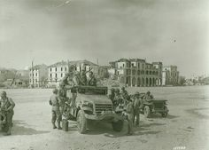 American troops along the Bizerte corniche shortly after the port fell. The town had been without running water for three months; typhus was present and cholera threatened. The M2 half track belongs to 9th Infantry Division, possibly 'B' Company of the 15th Combat Engineer Battalion, although the markings are not clear.