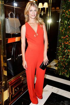 Melanie Laurent wears a red Tory Burch jumpsuit with a pendant necklace, black clutch, and sandals